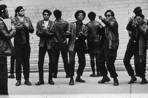 Archival photo of the Black Panther party wearing black berets, leather jackets, pants and combat boots
