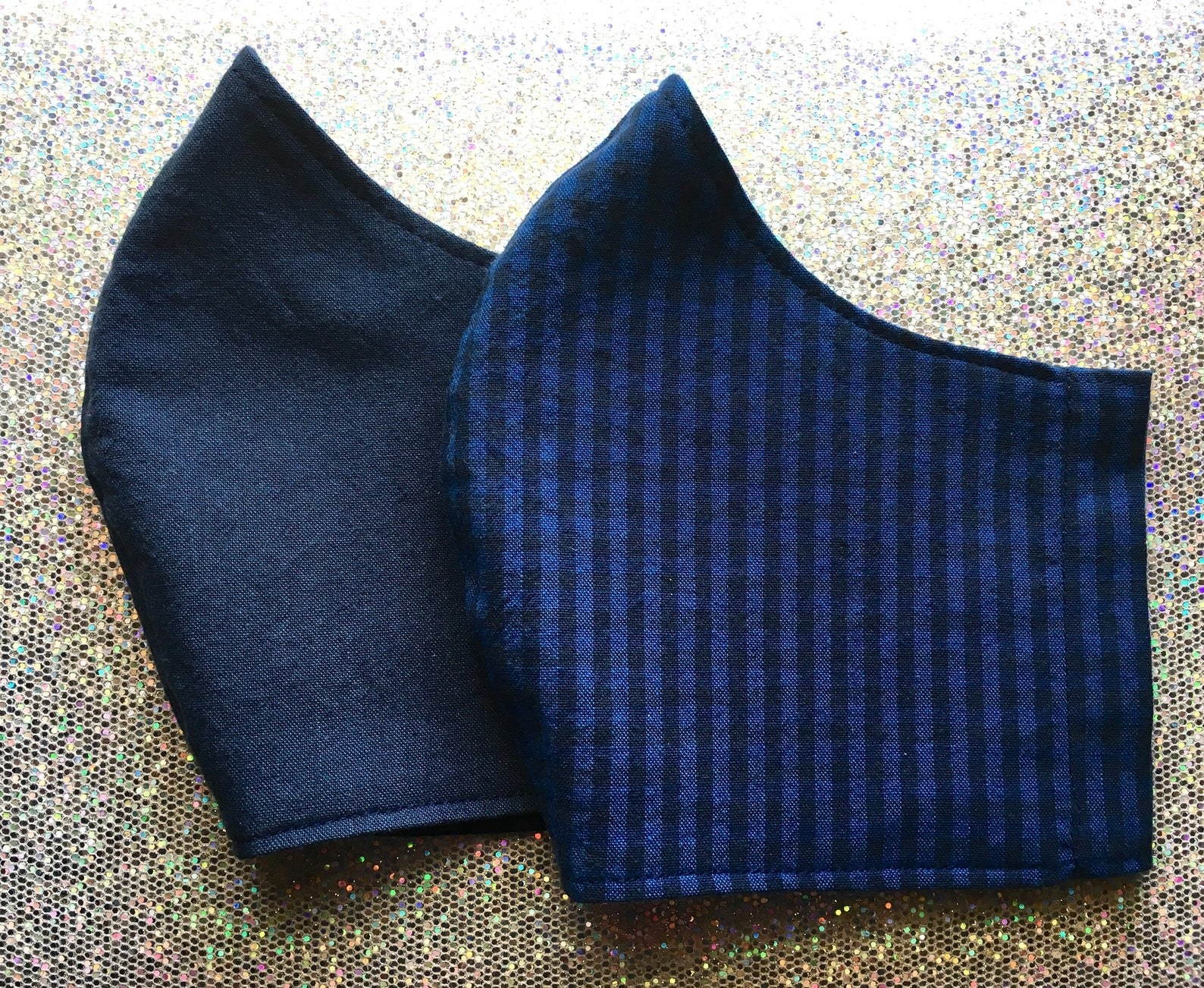A navy blue face mask and a navy blue/black gingham face mask