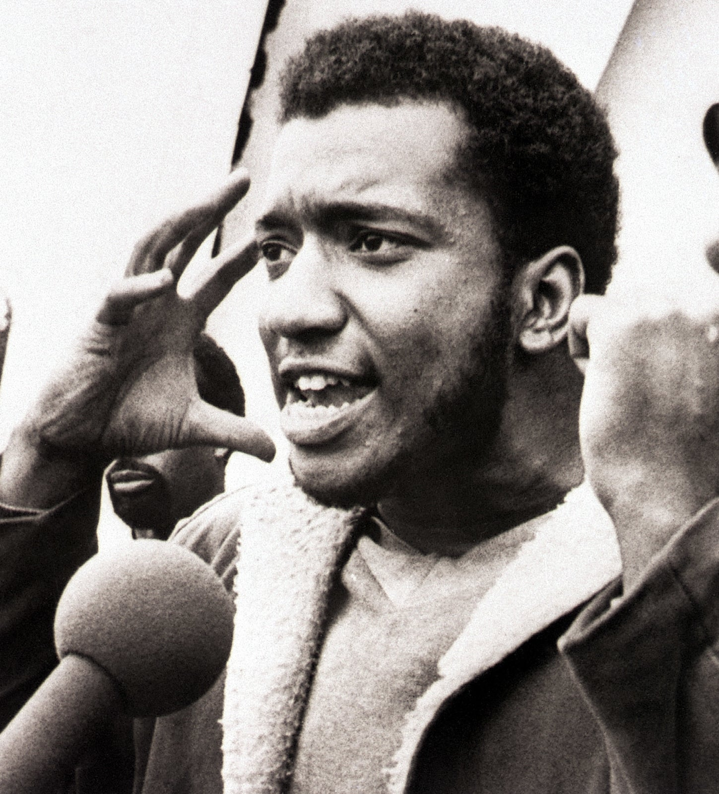 An archive photo shows Fred Hampton in the middle of saying something with his arms up.
