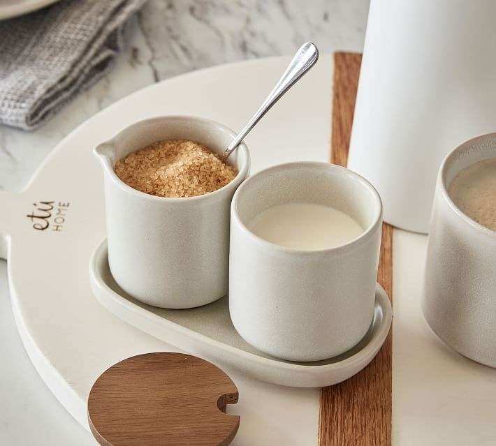 the white canisters holding sugar and cream and sitting on a stoneware tray