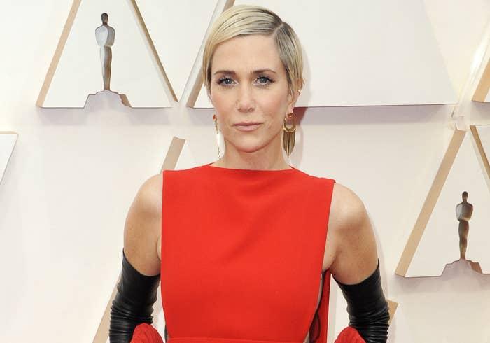 Kristen wears a red sleeveless dress to an event