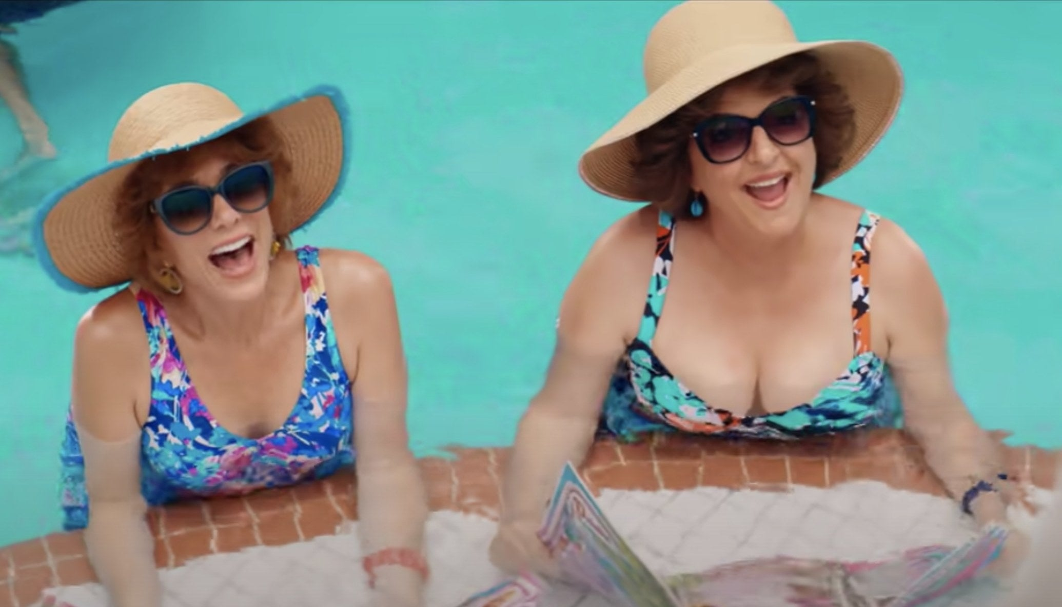 Barb and Star sit in a pool in multi colored bathing suits and large straw hats