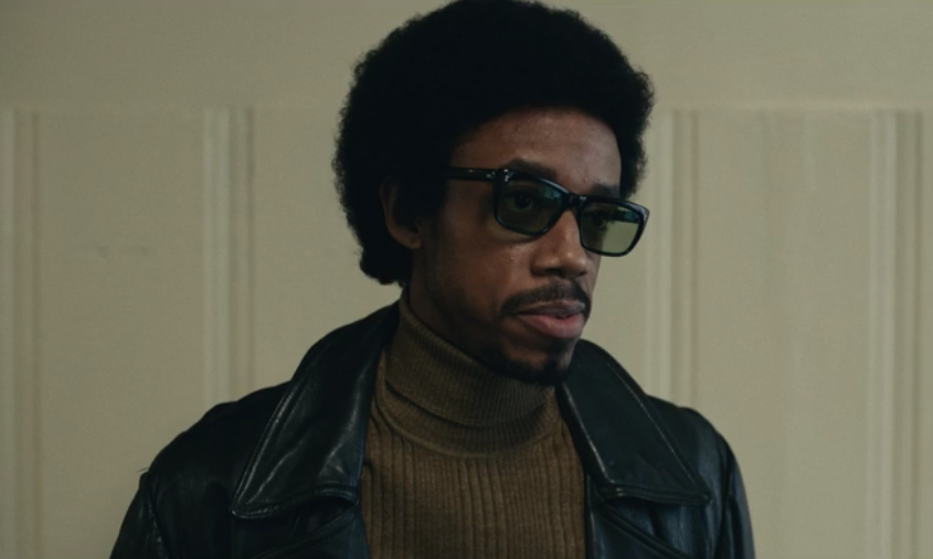 Bobby Rush wearing dark sunglasses, a black leather coat, and brown turtle neck