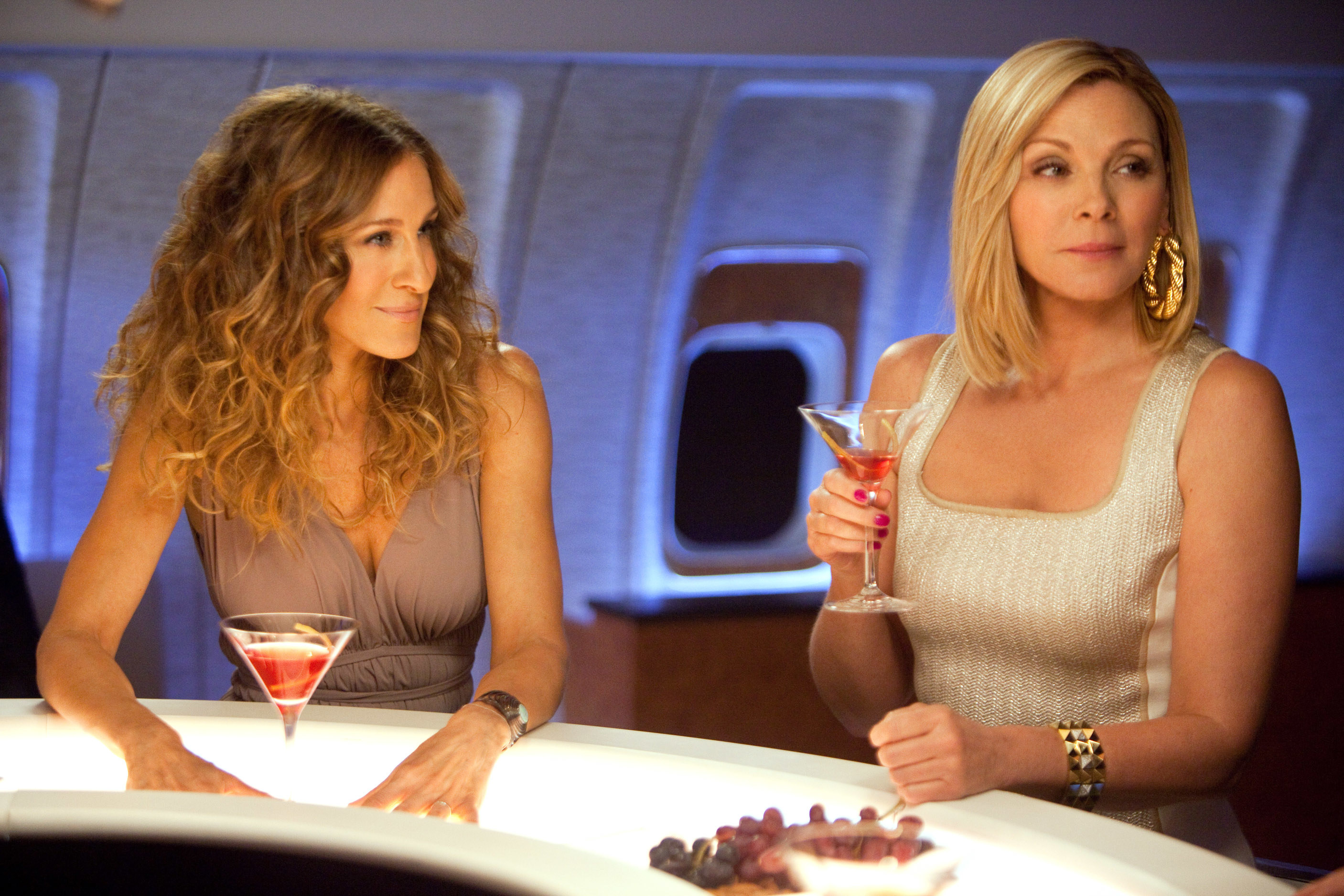 Carrie and Samantha drinking cosmos on an airplane