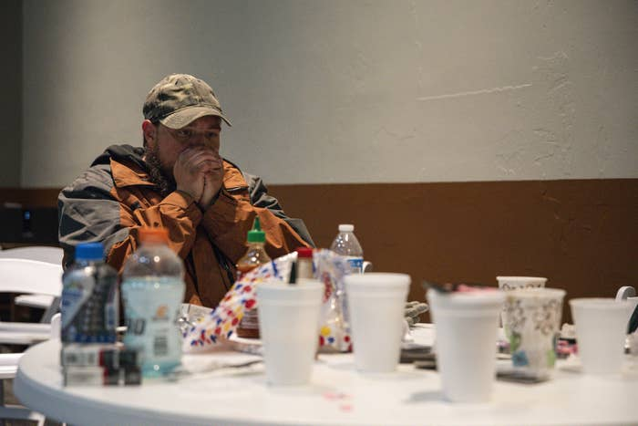 A man sitting indoors wearing a jacket and cap exhales into his hands, cupped over his mouth, in an effort to keep warm