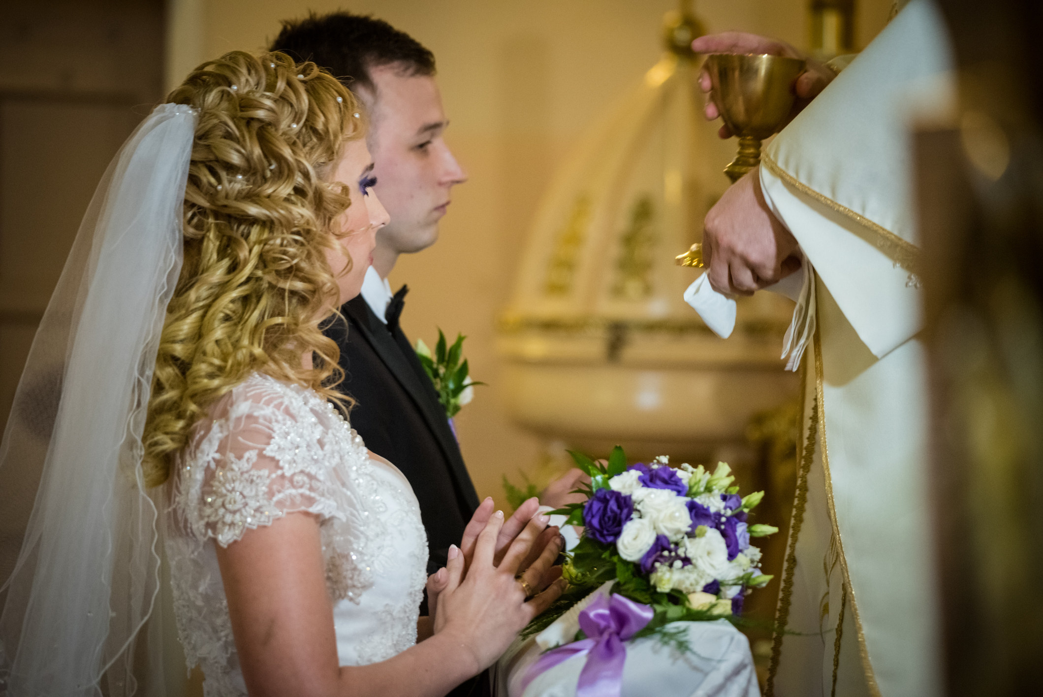 Bride and groom kneeling in front of altar during wedding ceremony and receiving communion