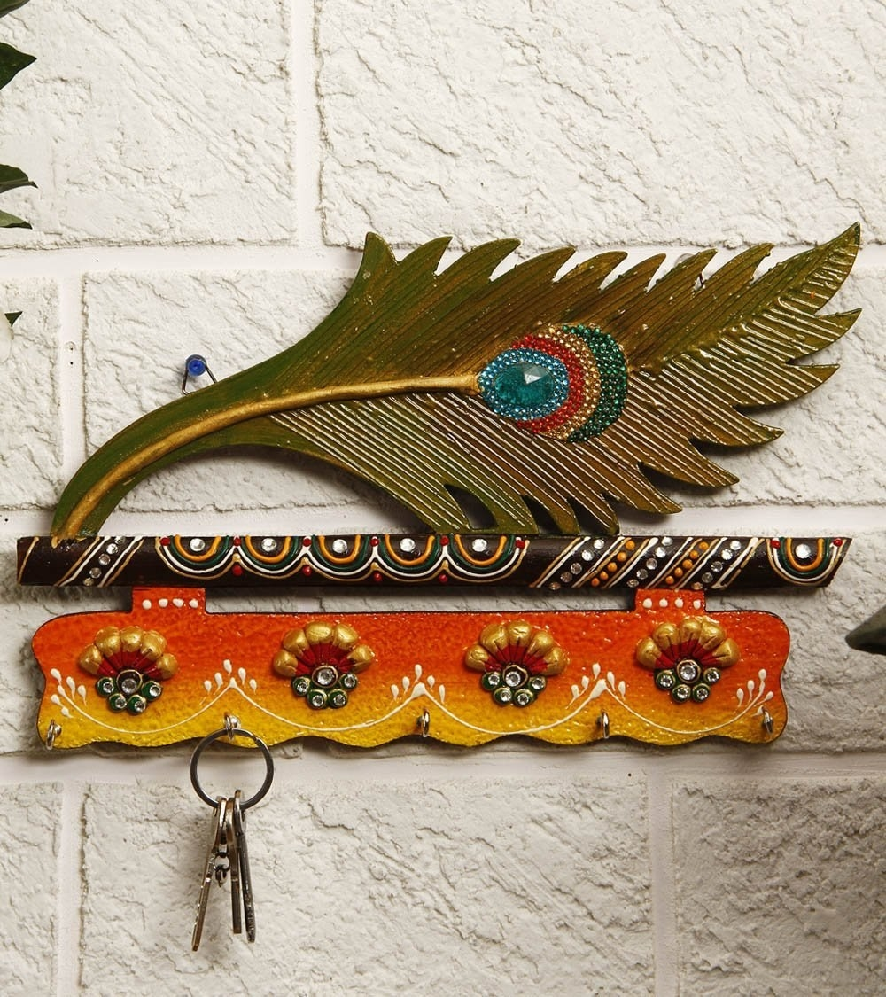 A peacock feather key holder on the wall