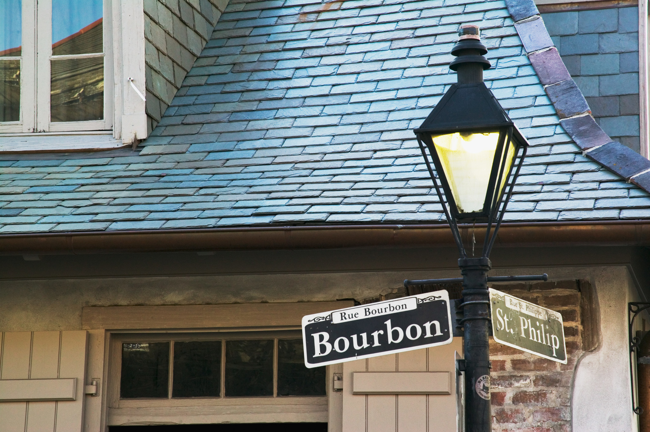 Bourbon Street sign with the haunted Lafitte's Blacksmith Shop in the background