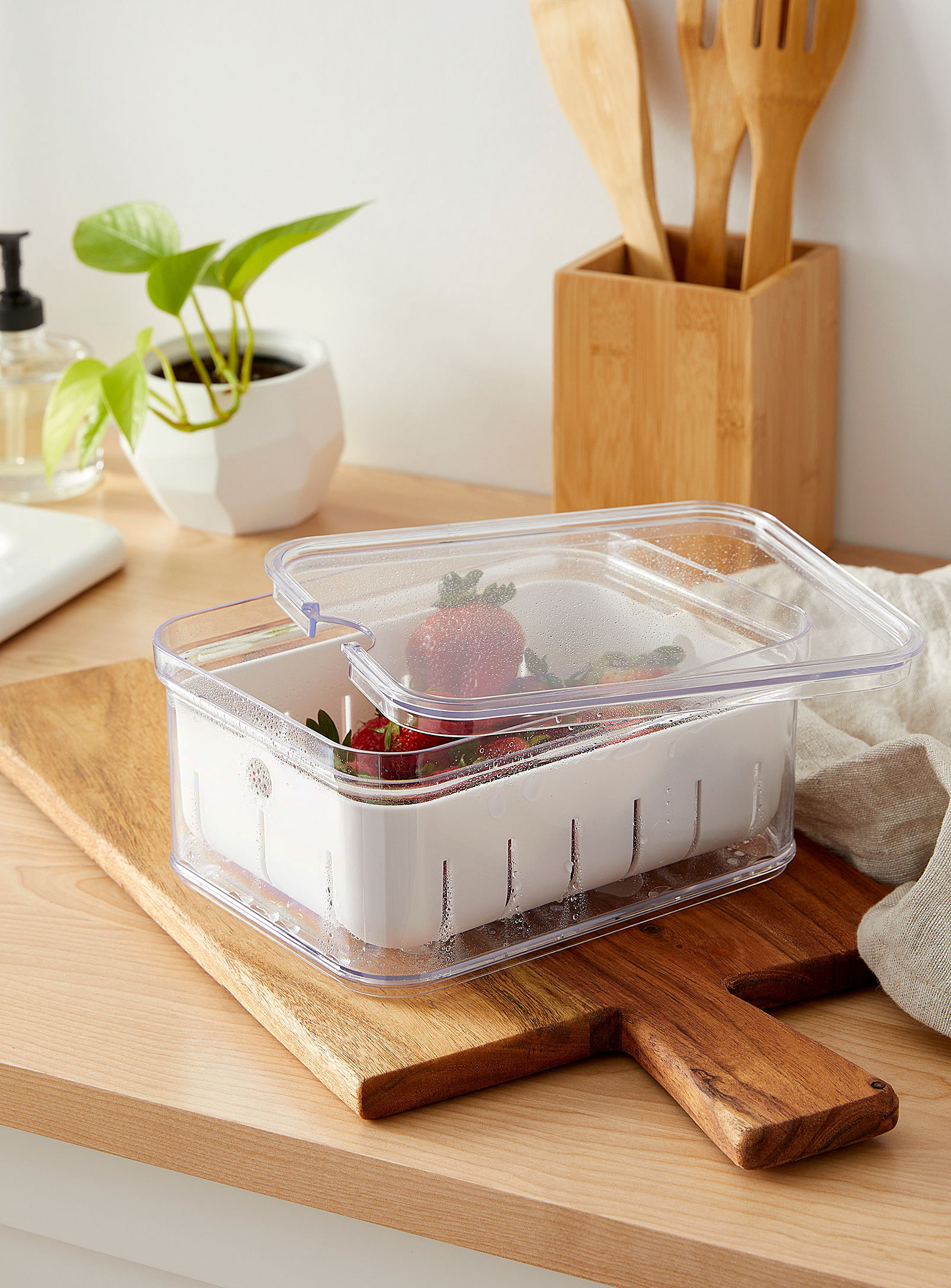 A small container filled with strawberries on a wooden counter