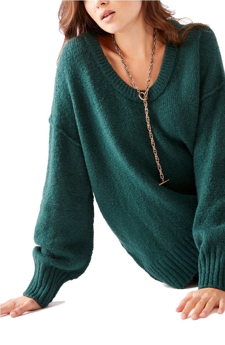model wearing a jewel green slouchy sweater while sitting on the floor
