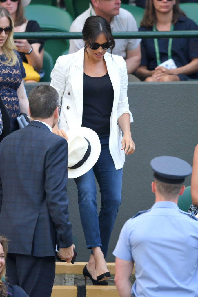 Meghan walking down stairs, wearing sunglasses, jeans, a white jacket, and high heels