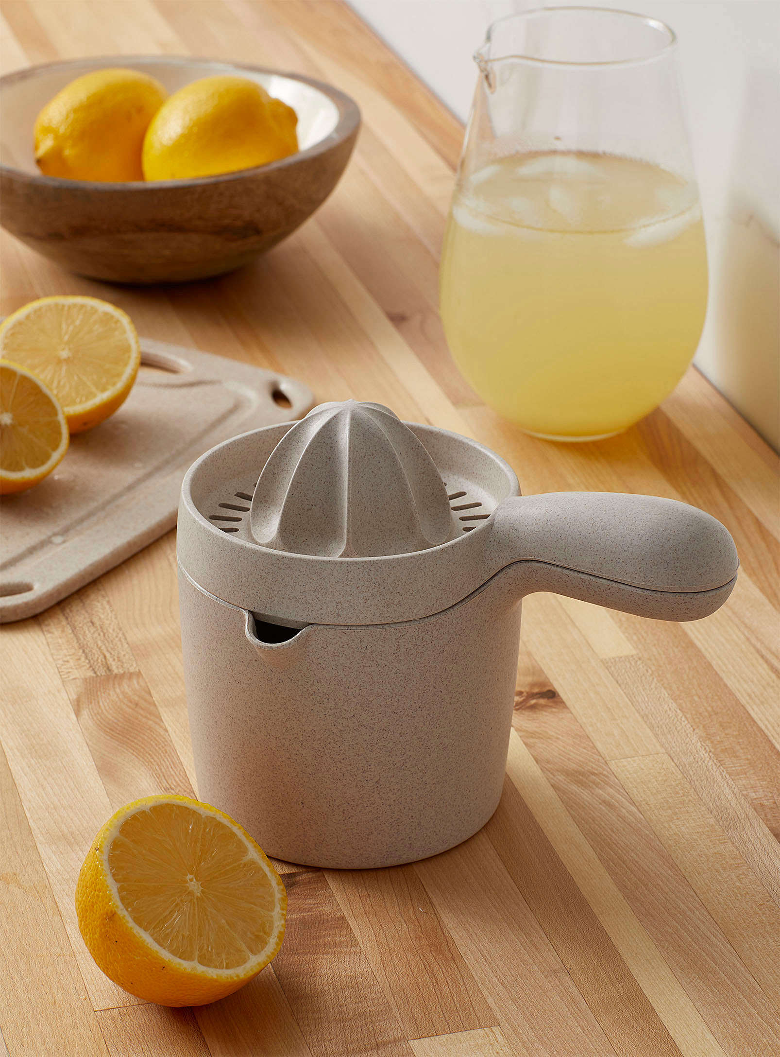 A small citrus press with a handle on top of a small measuring cup with an half cut lemon beside it
