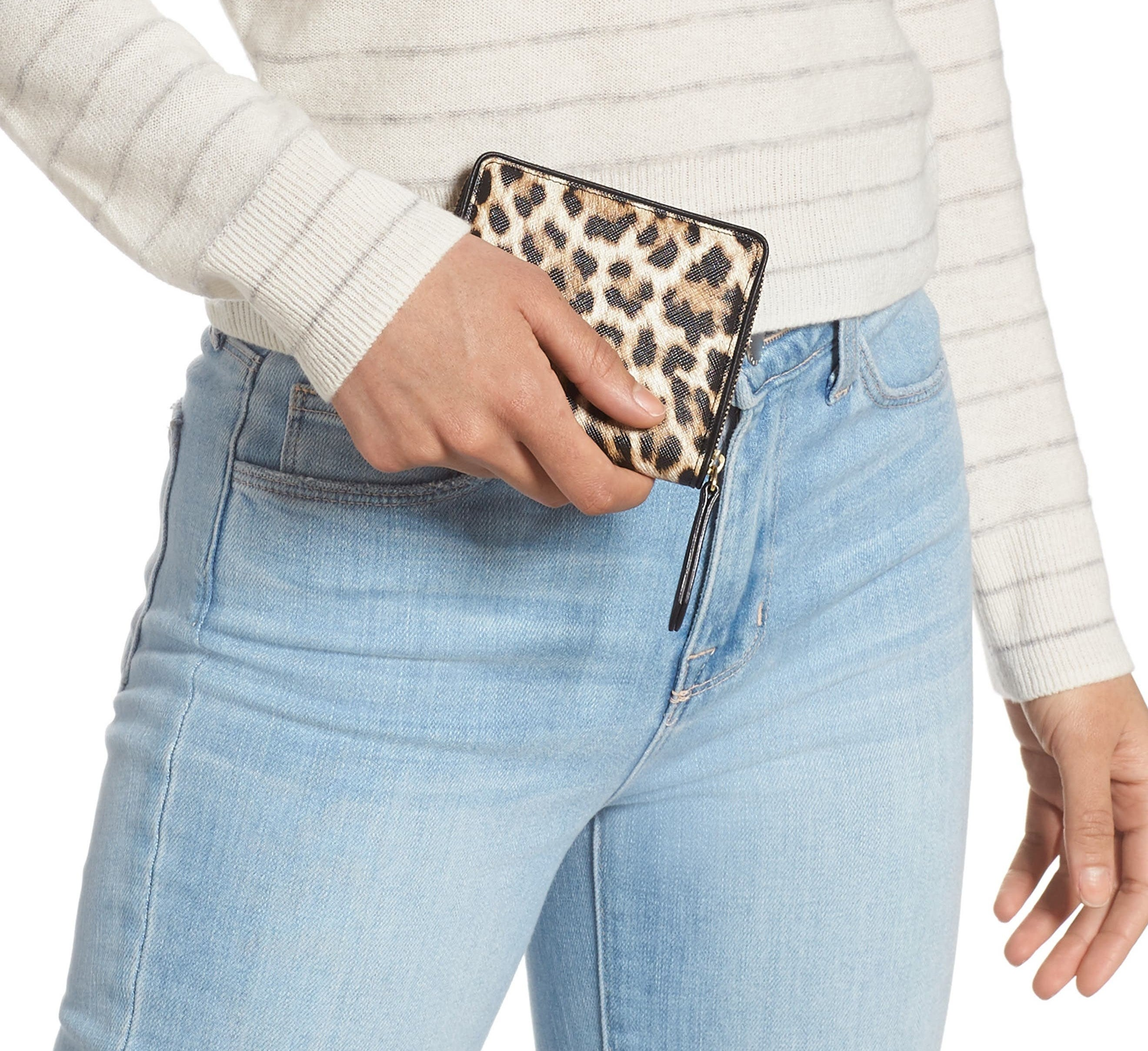 person holding a faux leather wallet on their hand