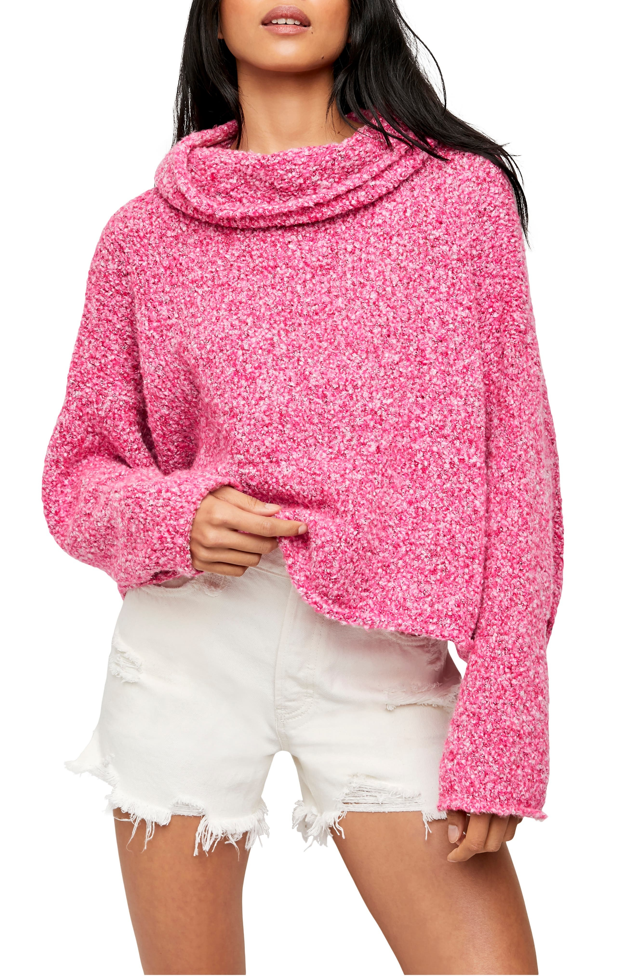 model wearing a pink cowl neck sweater and white cut-off jeans