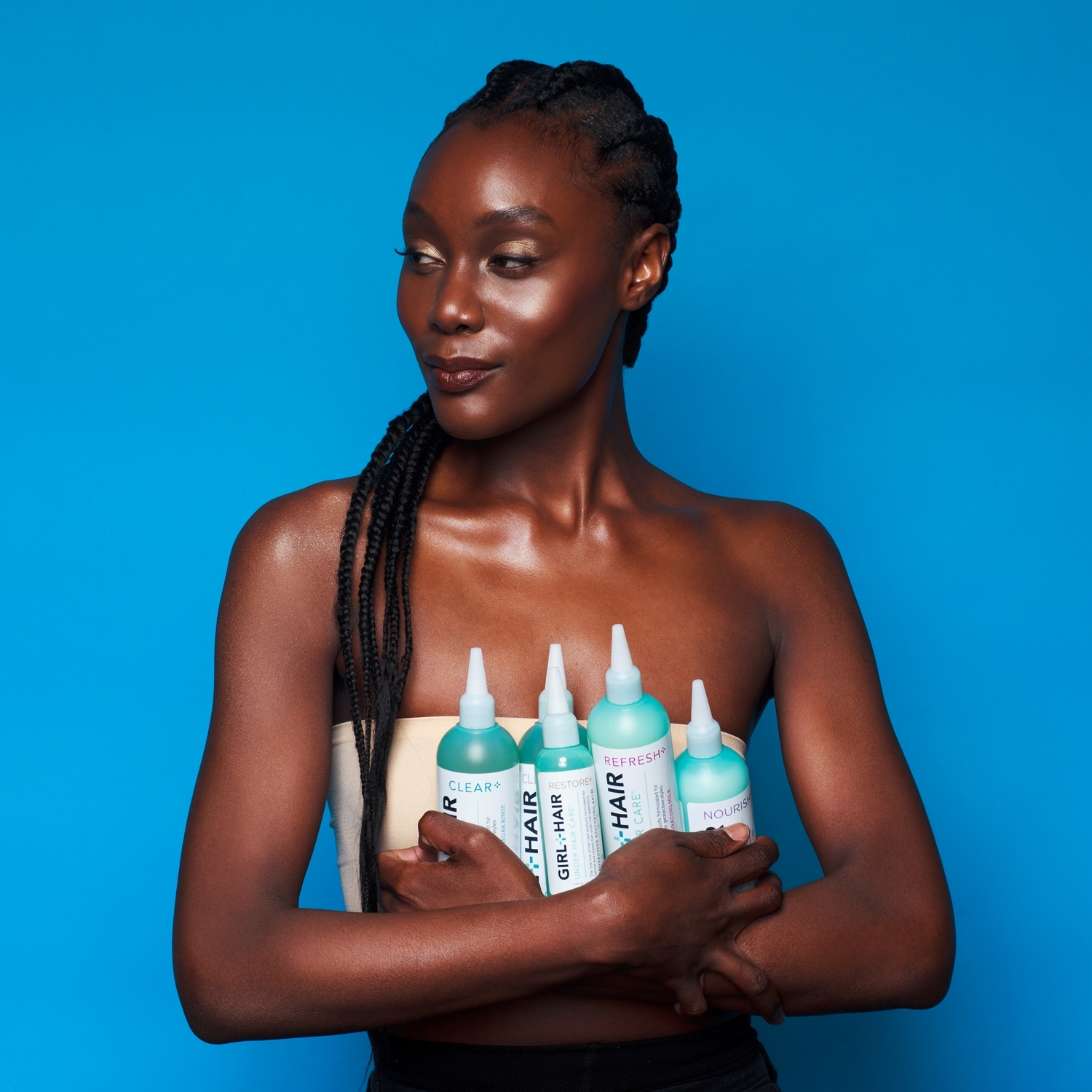 model holding the five bottles of hair care included in the set