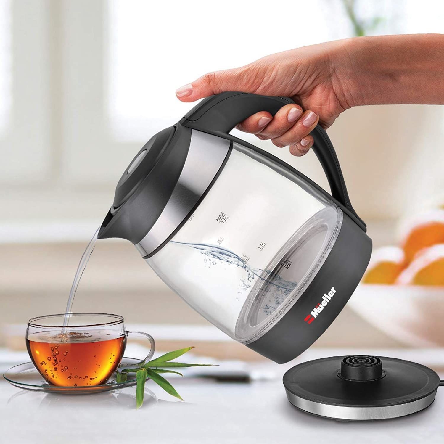 Model's hand pouring tea kettle with black base and lid
