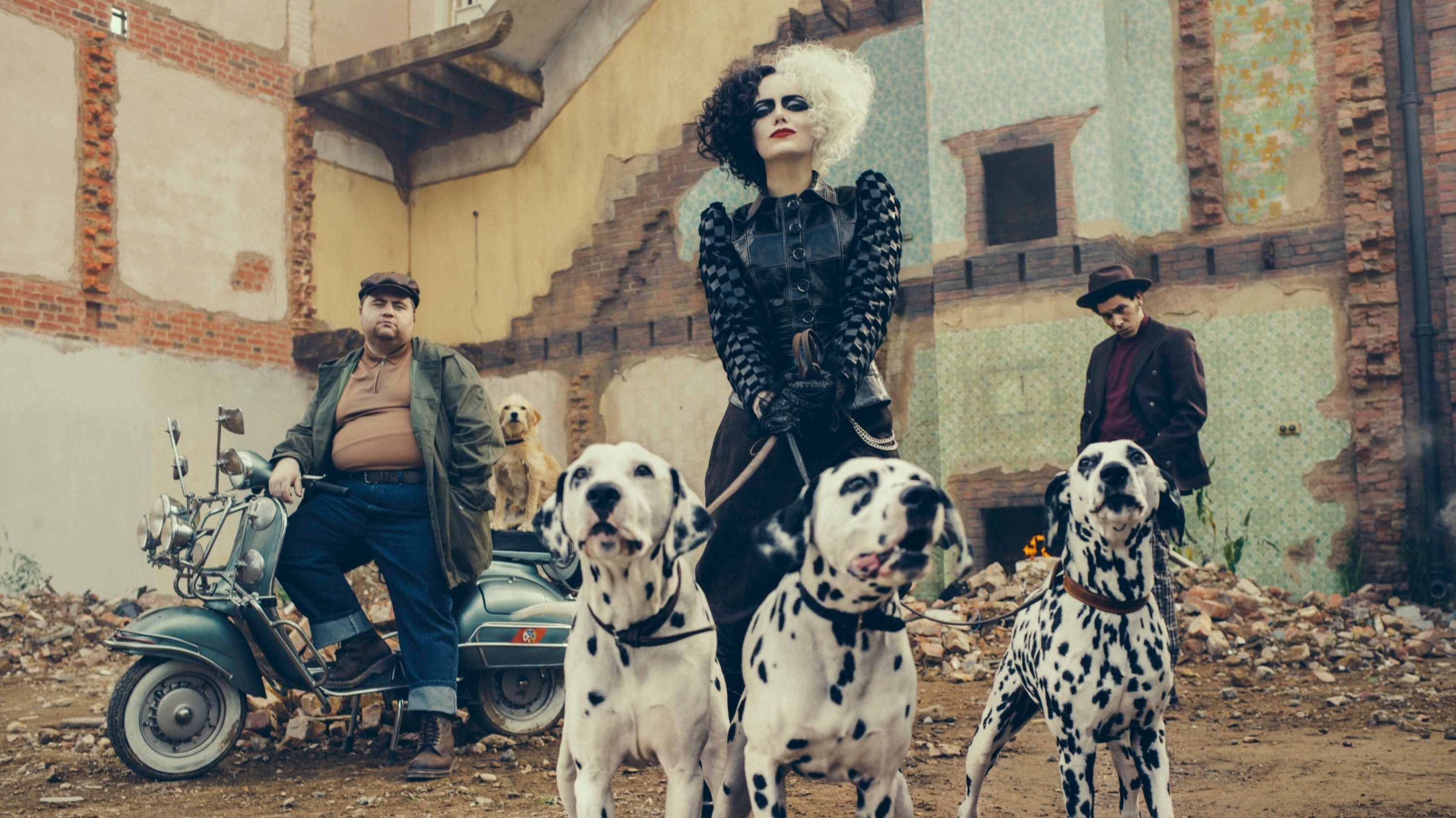 Emma as Cruella de Vil holding the leashes of three Dalmatians in an abandoned yard and two henchmen standing behind her