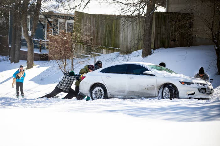 Several people try to push a car through the snow in front of a house