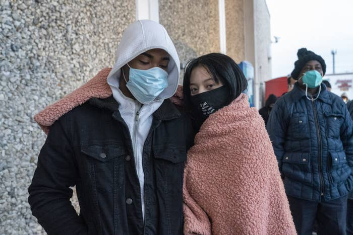 Two people wearing face masks and sharing a blanket around their shoulders
