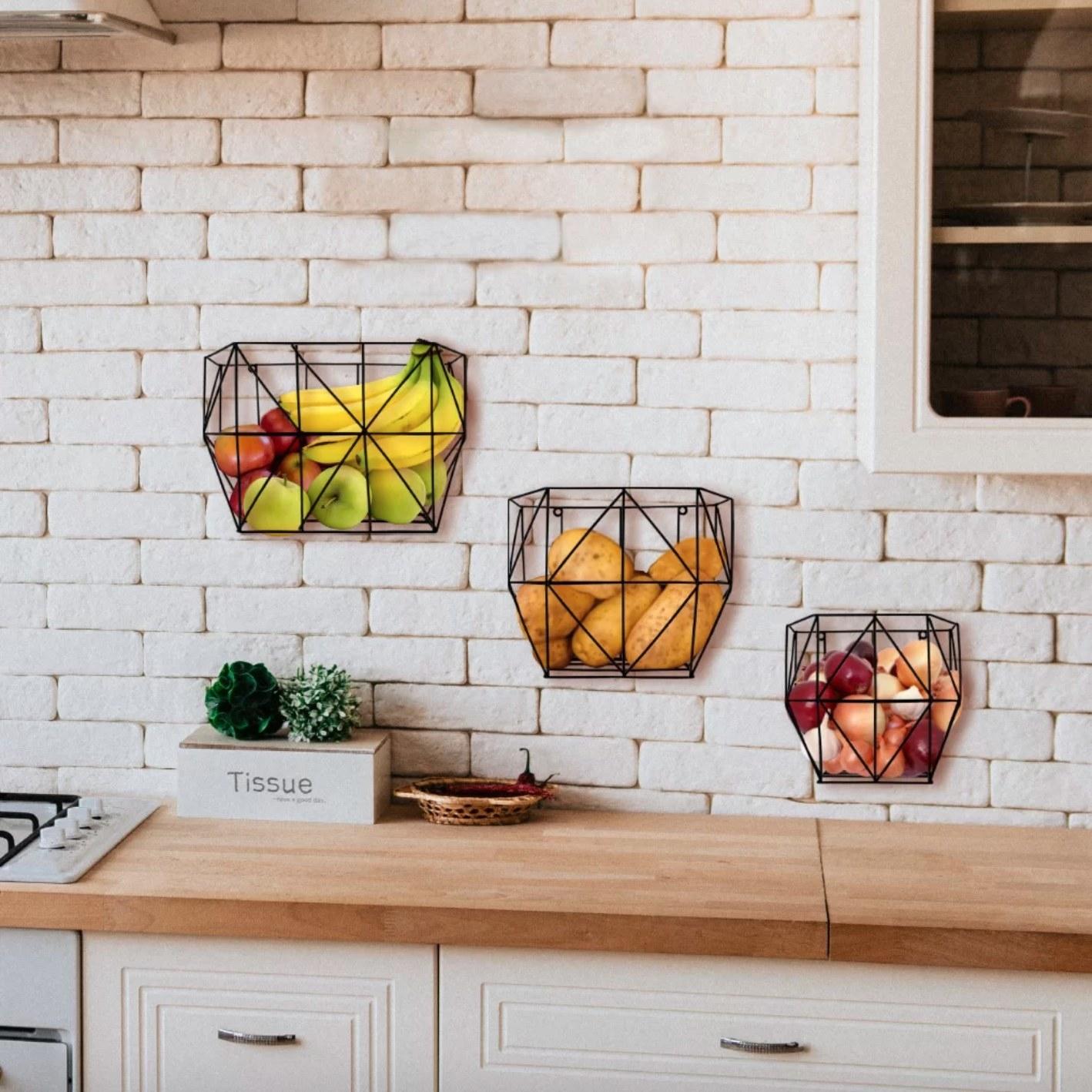 three metal wall baskets holding produce