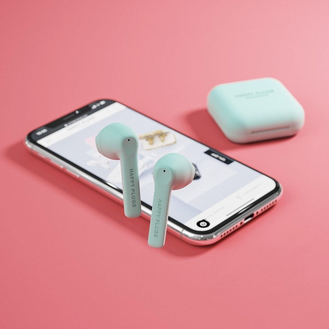 The mint green headphones in front of a phone