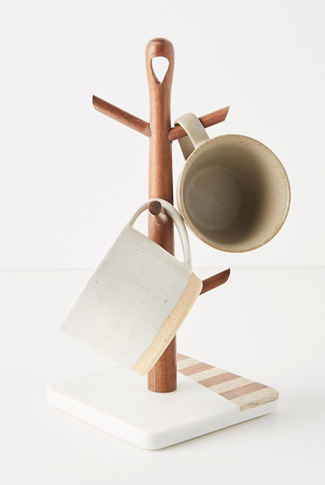 A white based mug tree with pink and ivory striped designs and a light wood stem with branches to hold mugs