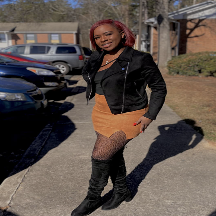 customer wearing skirt with moto jacket, tights, and boots