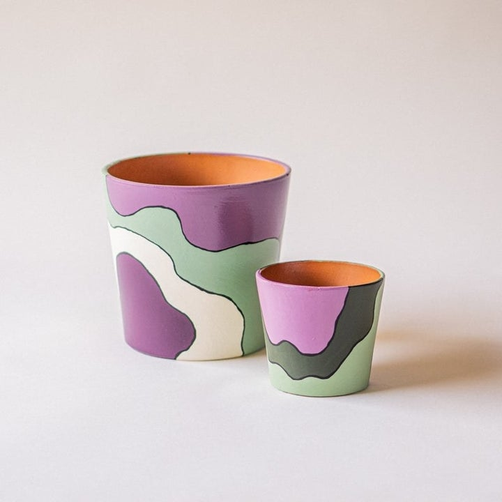 A purple, green, and white abstract painted pot