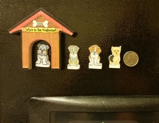 """A magnet shaped like a doghouse that says 'Who's in the doghouse?"""" and four dog-shaped magnets with a quarter next to them for scale"""