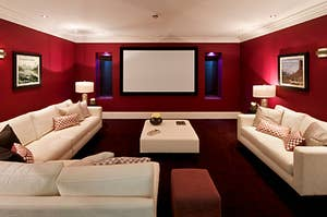 A movie room with red walls and big white couches