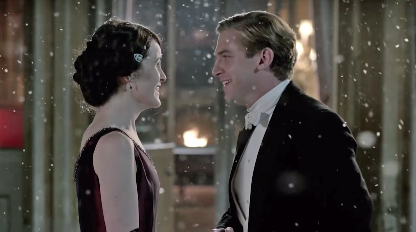 Mary and Matthew smile at each other as the snow comes down around them