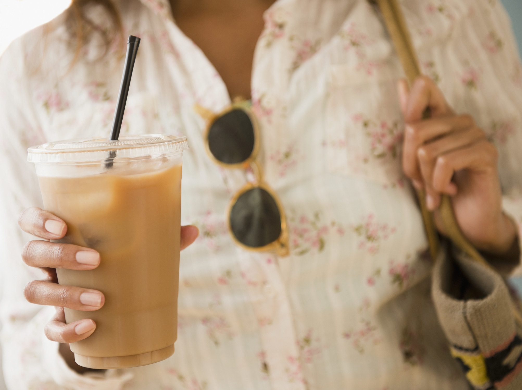 A woman holding an iced coffee drink