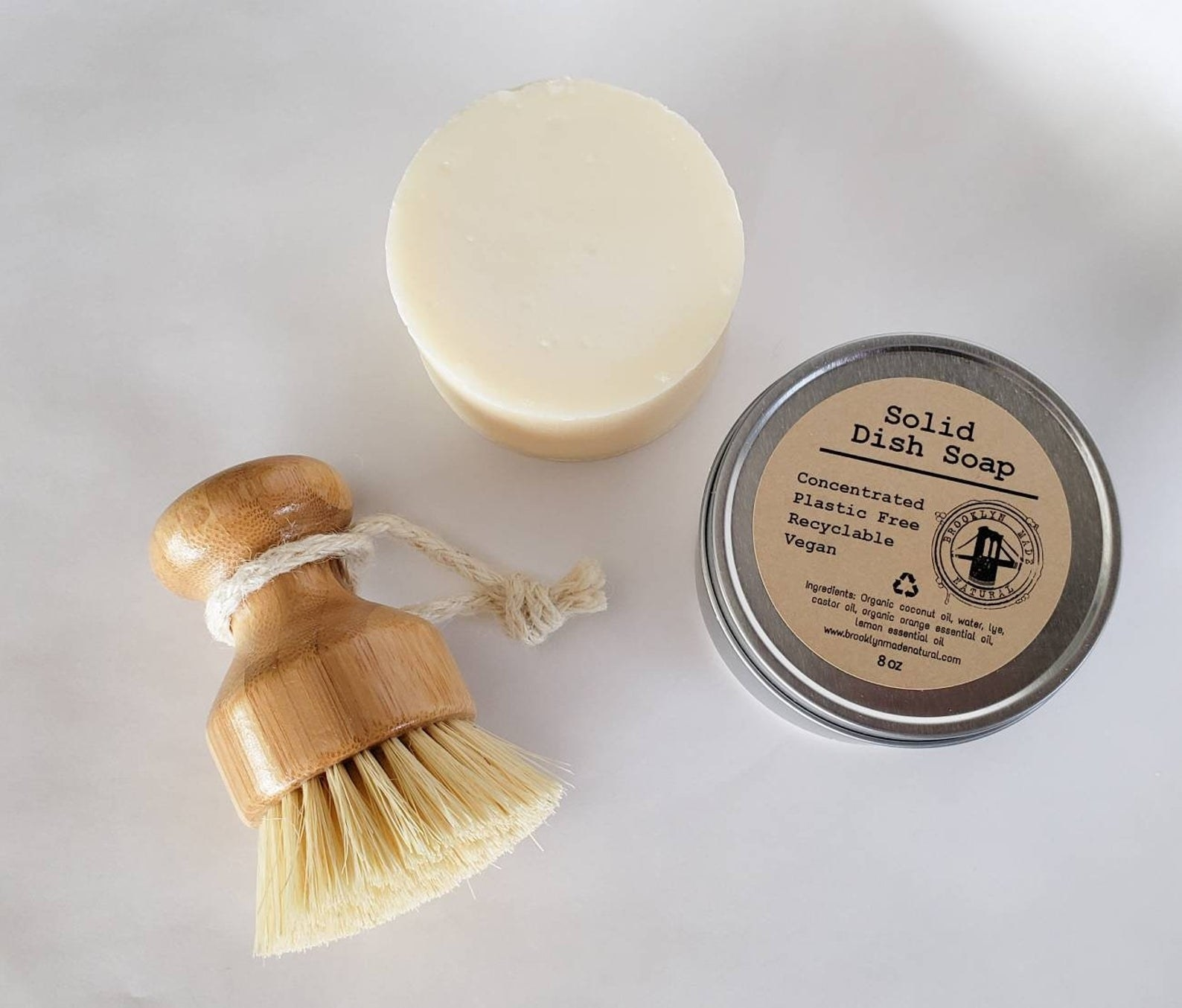 Solid dish soap in tin next to dish brush
