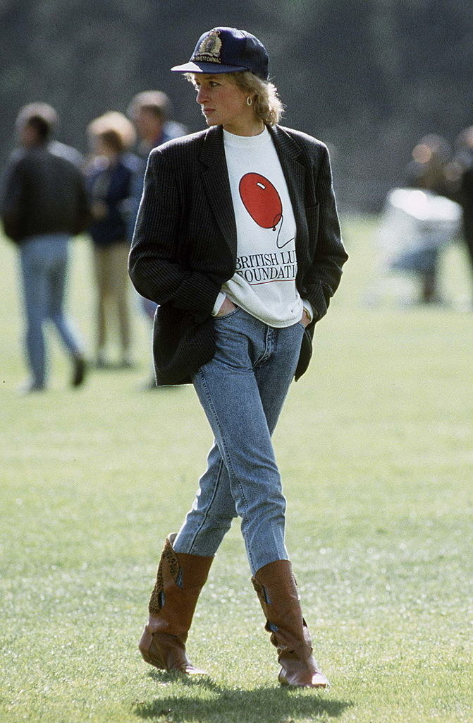 Diana wears mom jeans, a t-shirt, a blazer, a cap, and boots