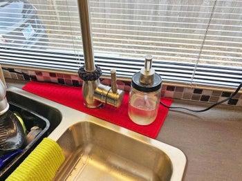 Red drip catcher placed around kitchen sink's faucet