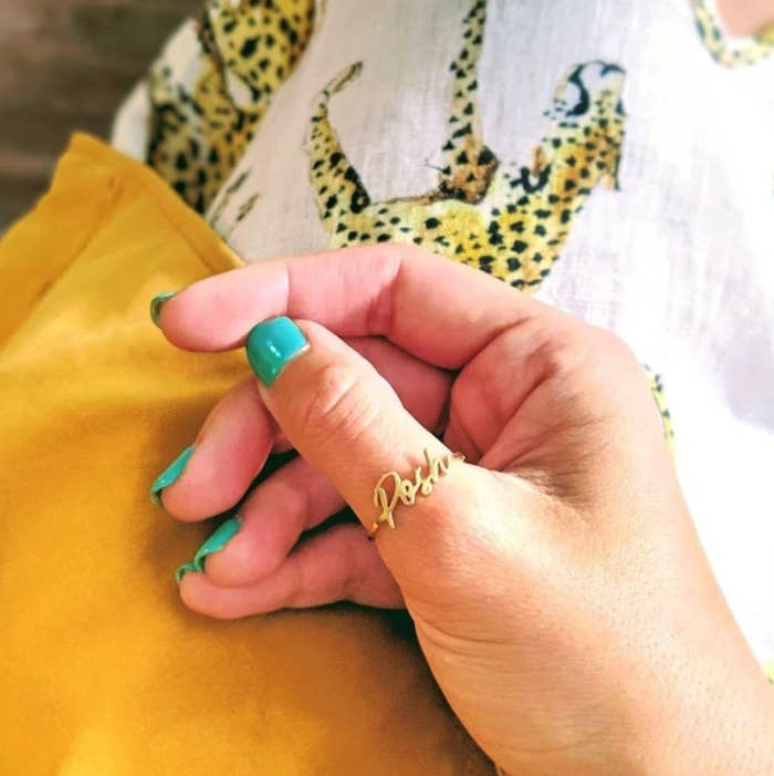 hand wearing the custom gold signature ring on their thumb