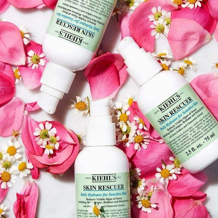 A flatlay of several bottles of the skin cream surrounded by rose petals and chamomile flowers