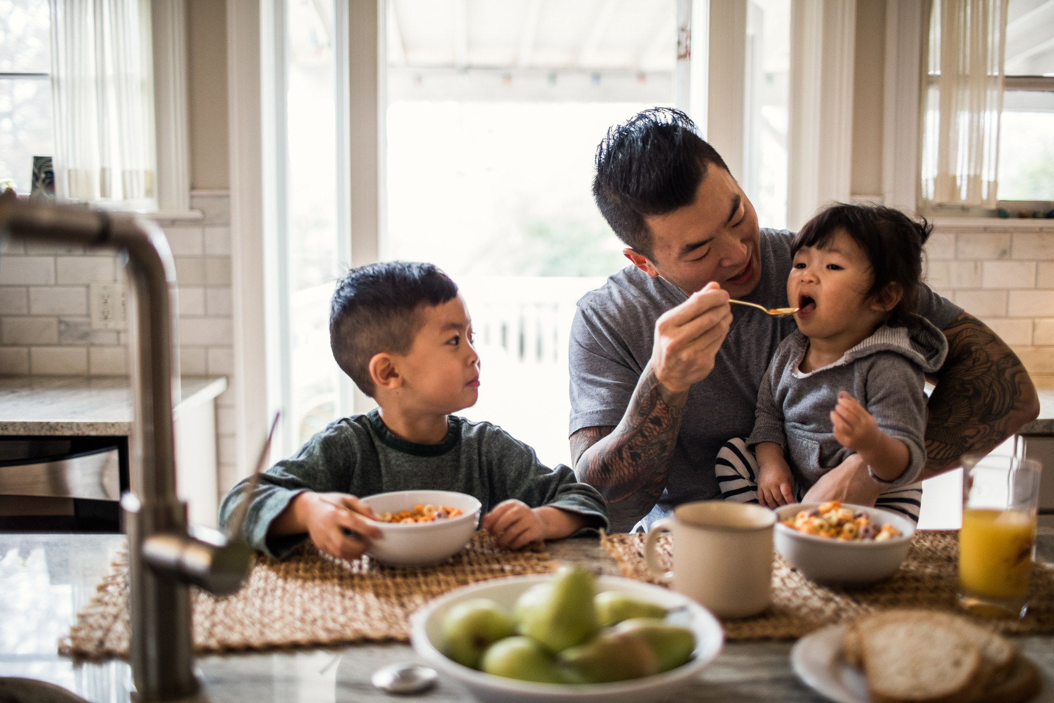 Stay-at-home dad eating breakfast with two kids