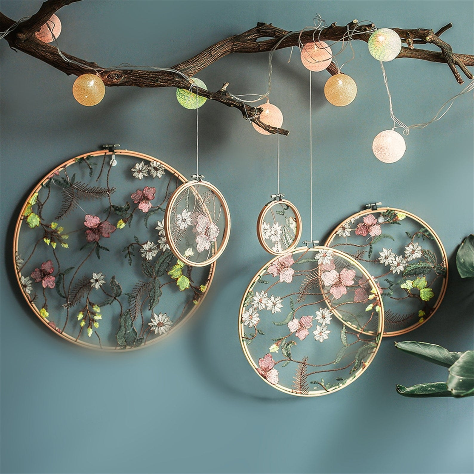 Embroidered flowers in a transparent background in a light wooden hoop hanging from the ceiling