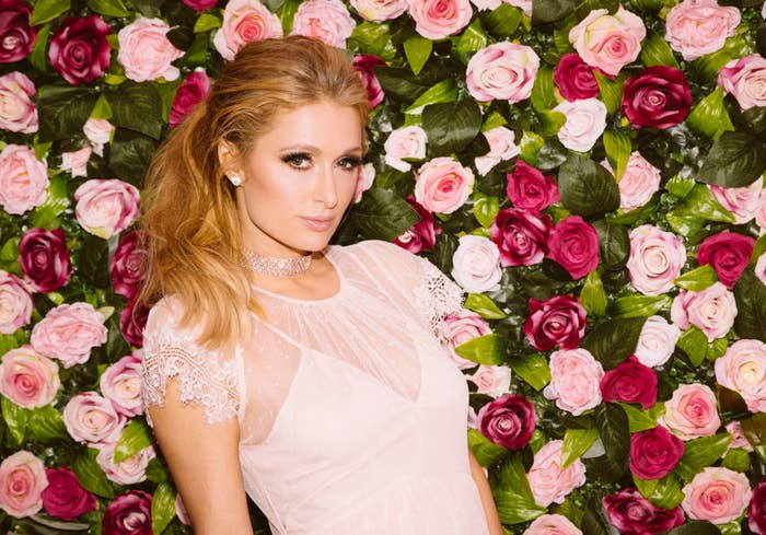 Paris posing against a backdrop wall of roses