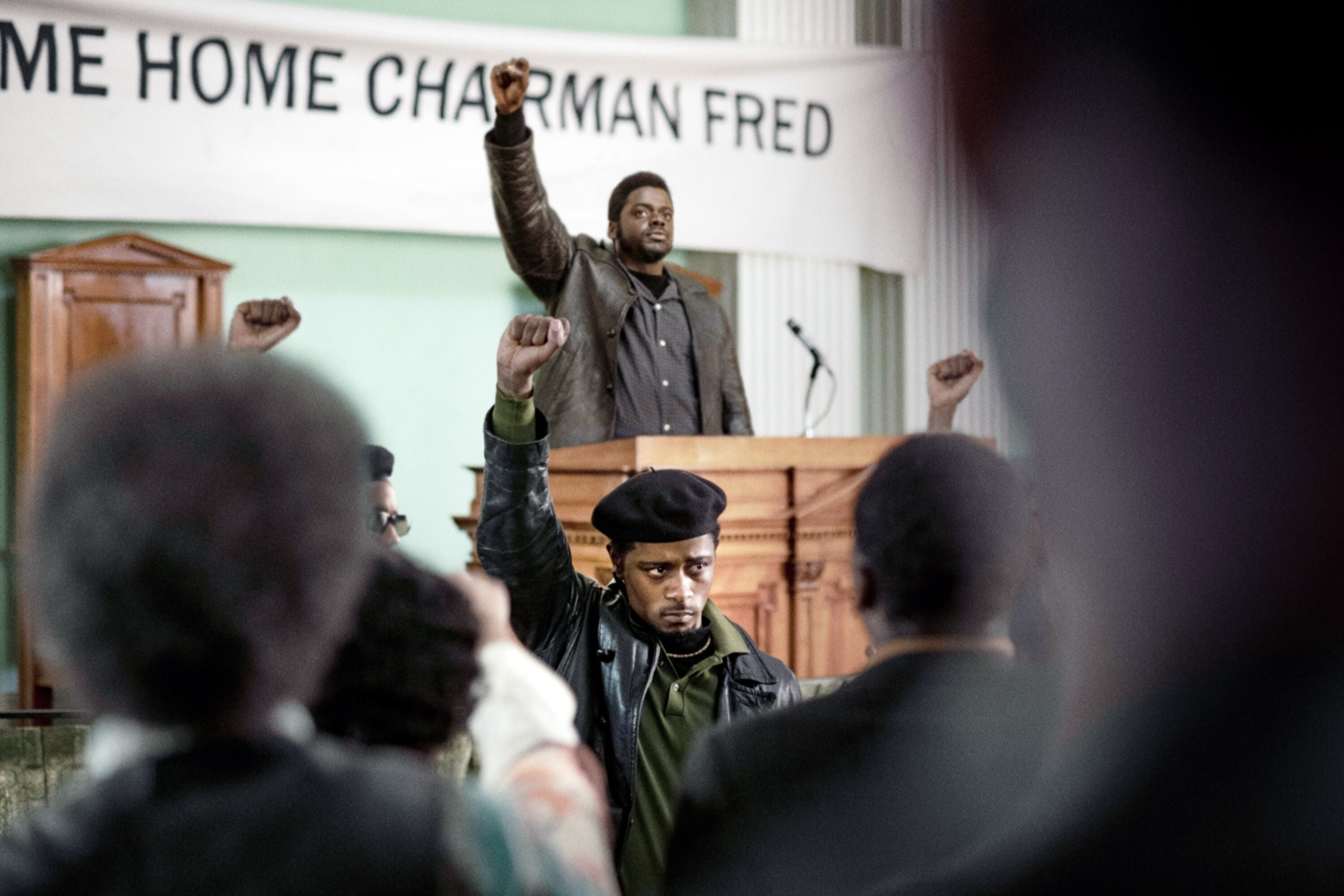 LaKeith Stanfield as William O'Neal raises his fist in the air, mirroring the same pose as Daniel Kaluuya as Fred Hampton, who is standing on a stage behind him