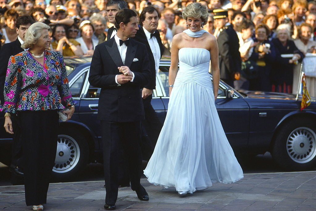 Princess Diana wearing a strapless, long white gown and walking alongside Prince Charles