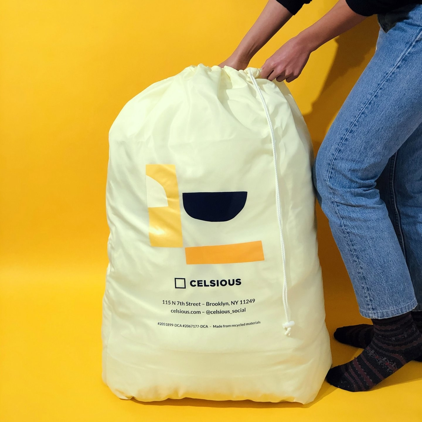 closeup of a full celsious extra large laundry bag against a bright yellow backdrop
