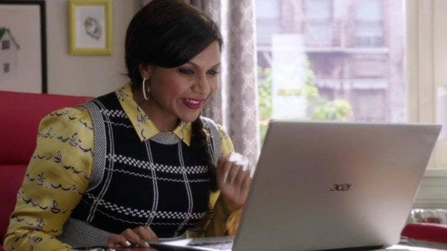 woman wearing dress with sweater vest over it leans over a laptop, smiling with her teeth showing