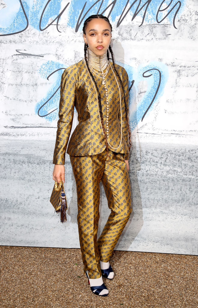 FKA Twigs wearing a patterned suit, heels with socks, and a matching patterned purse