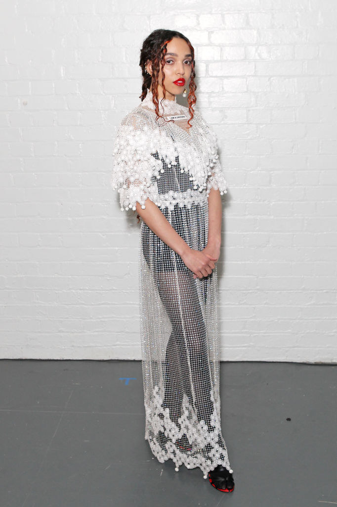 FKA Twigs posing in a sheer gown and tights