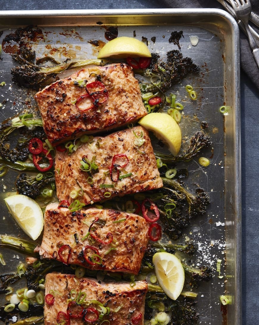 Broiled salmon with peppers and scallions and broccolini on a sheet pan.