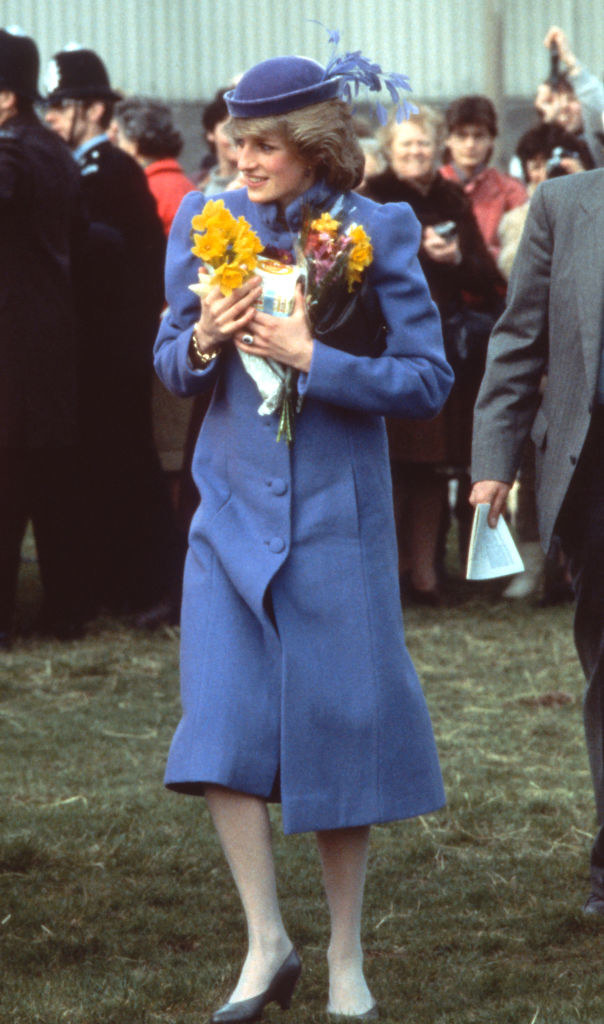 Diana wears a long, puffy coat and a hat with silk flowers