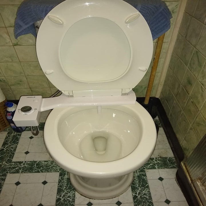 A bidet attachment in silver with the seat up