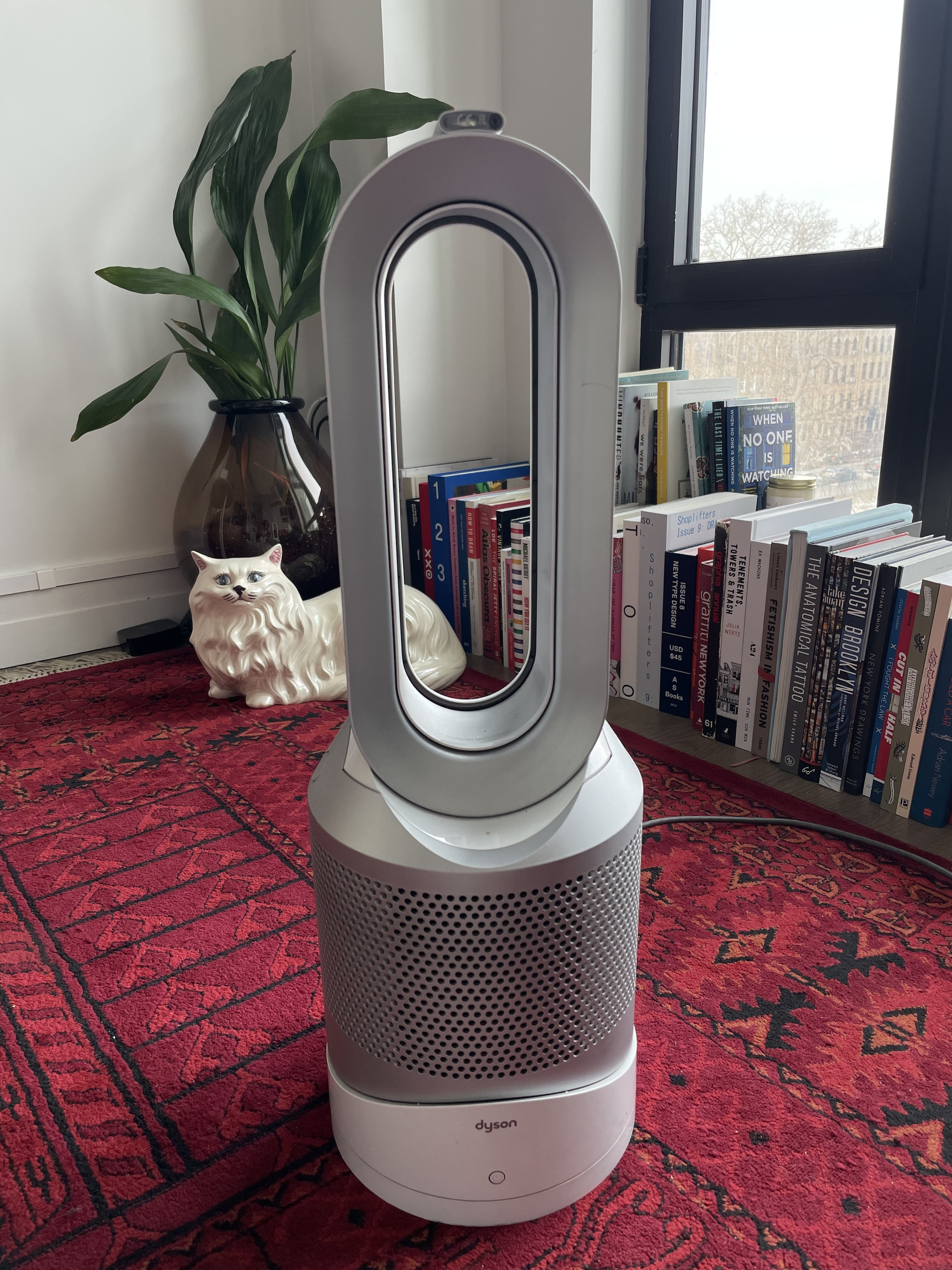 Mal's Dyson in her living room. It is oval shaped with a small footprint and plugged into the wall.